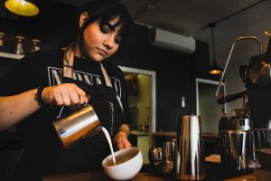 Barista pouring milk into coffee