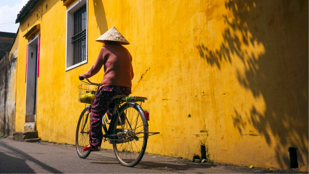Vietnamese woman cycling, Hoi An old town, Vietnam